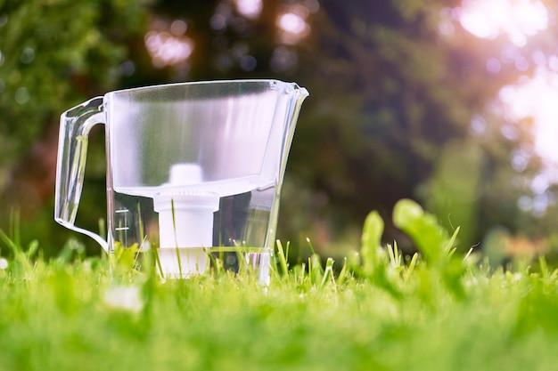 Dzbanek z filtrem wody stojący na zielonej trawie w letnim ogrodzie w ciepły poranek. koncepcja filtracji wody.
