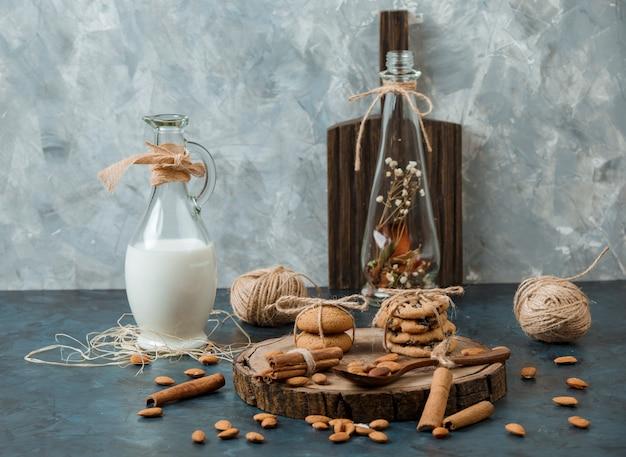 Dzbanek z mlekiem migdałowym, cynamonem, domowymi i czekoladowymi ciasteczkami, drewnianą łyżką i orzechami na desce
