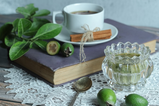 Dżem feijoa i filiżankę herbaty na drewnianym stole.