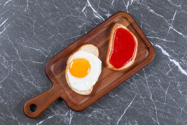Dżem i jajka sadzone na dwóch kromkach chleba na desce, na marmurowej powierzchni