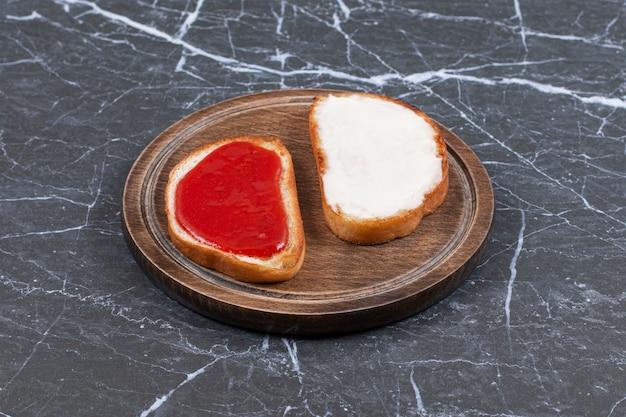 Dżem i ser na dwóch kromkach chleba na desce, na marmurowej powierzchni