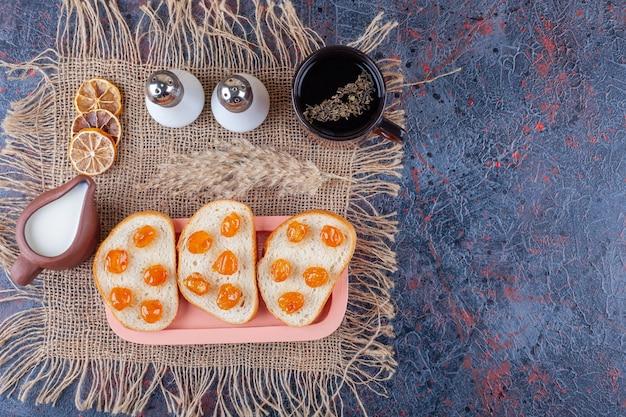 Dżem na krojonym chlebie na desce na jutowej serwetce obok materiału, na niebieskim tle.