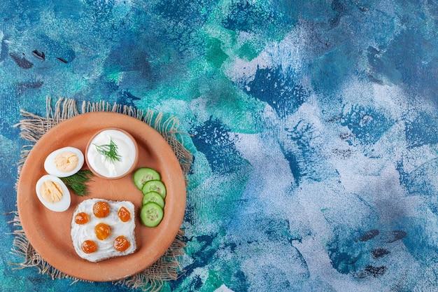Dżem na krojonym chlebie obok pokrojonego jajka, ogórek na talerzu na jutowej serwetce, na niebiesko.