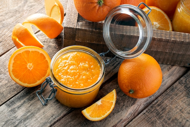 Dżem pomarańczowy w słoiku na drewnianej ścianie.