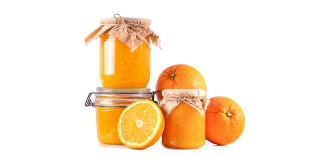 Dżem pomarańczowy w szklanych słoikach na białej ścianie na białym tle.