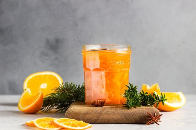 Dżem pomarańczowy w szklanym słoju z zimowymi przyprawami i gałęziami jodły.