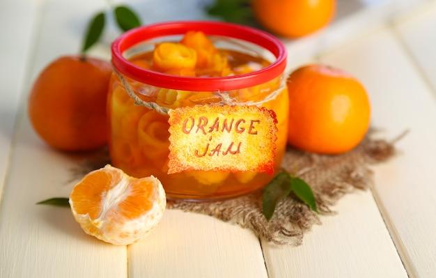 Dżem pomarańczowy ze skórką i mandarynkami na białym drewnianym stole