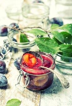 Dżem śliwkowy w słoiku. marmolada owocowa. stonowany obraz w stylu vintage