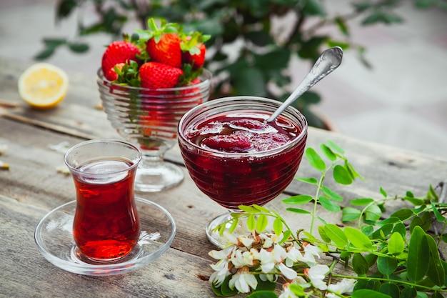 Dżem truskawkowy z łyżką, szklanką herbaty, truskawkami, cytryną, roślinami w talerzu na drewnianym i chodnikowym stole, wysokiego kąta widok.