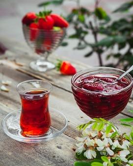 Dżem truskawkowy ze szklanką herbaty, łyżką, truskawkami, roślinami w talerzu na stole drewnianym i chodnika, wysoki kąt widzenia.