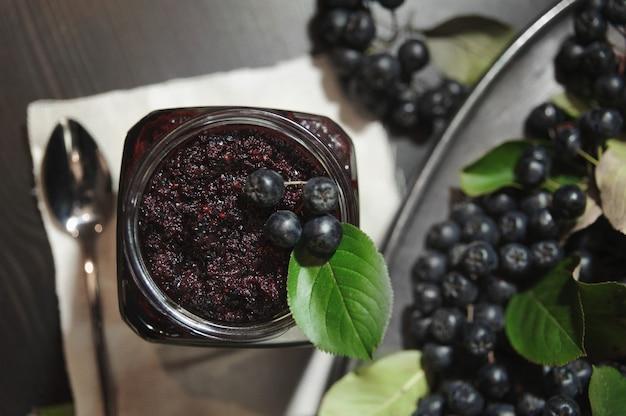 Dżem z czarnej aronii (aronia melanocarpa) i jej jagody na ciemnym stole. domowe przetwory.