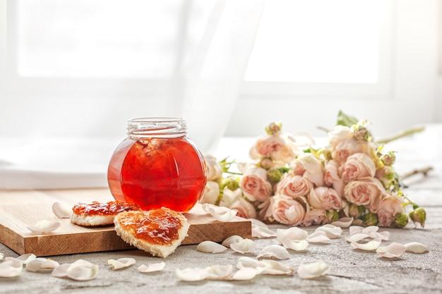 Dżem z płatków róży i kanapka w kształcie serca z marmoladowym kwiatem róży na stole.