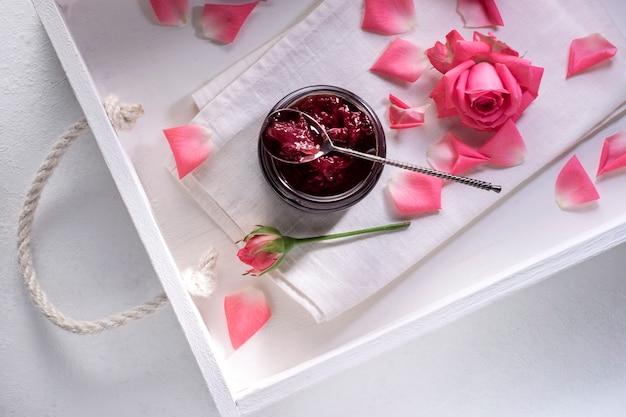 Dżem z różowych płatków róży w białej tacy na stole