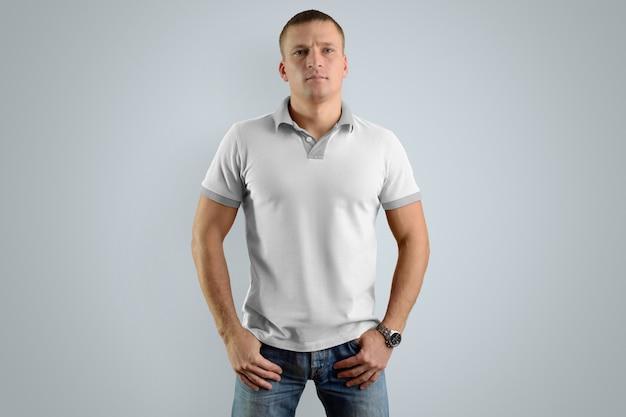 Dżentelmen w puste koszulki polo i niebieskie dżinsy z rękami w kieszeniach na białym tle na szarej ścianie, widok z przodu.