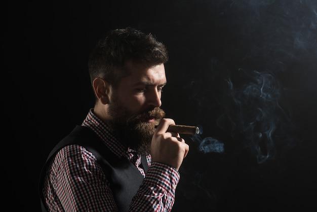 Dżentelmen z brodą i wąsami pali cygara fryzjera koncepcja tlącego się cygara palącego człowieka na