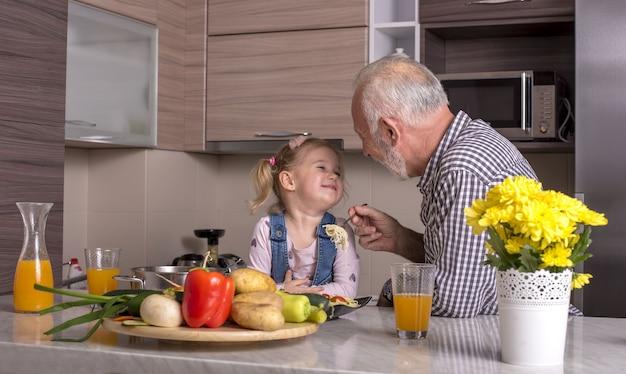 Dziadek bawi się z wnuczką w kuchni