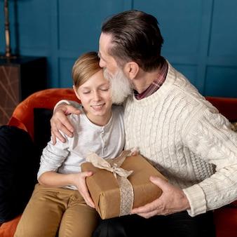 Dziadek całuje wnuka na czole