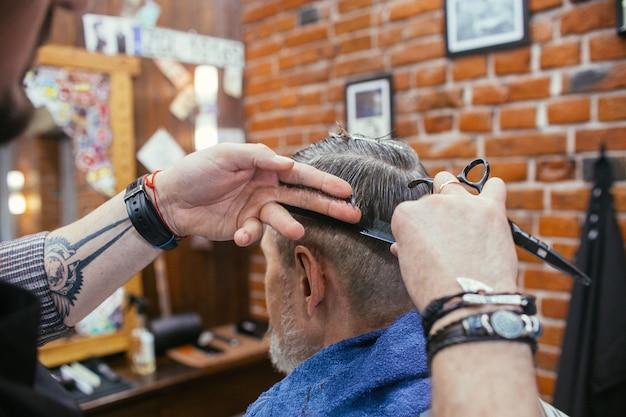 Dziadek dostaje fryzurę u fryzjera w sklepie fryzjerskim. modna fryzura starca, emeryta w sklepie fryzjerskim