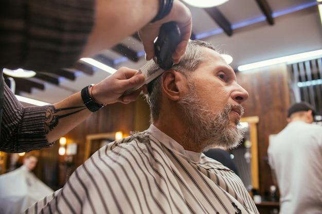 Dziadek dostaje fryzurę u fryzjera w sklepie fryzjerskim.
