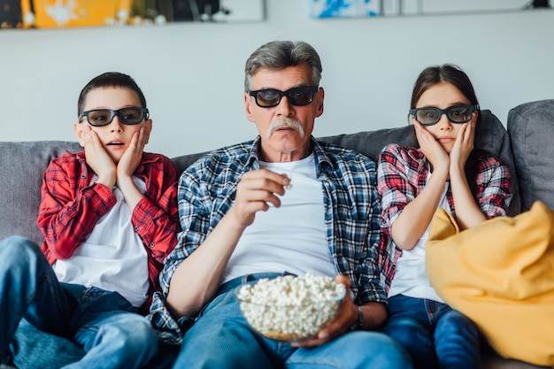 Dziadek eldery siedzący z wnukami na kanapie w salonie i oglądający horror, jedzący popcorn.