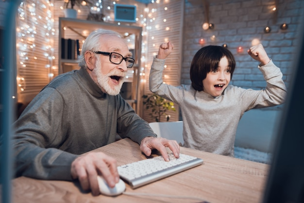 Dziadek grający w gry komputerowe z wnukiem