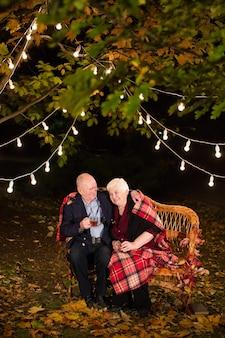 Dziadek i babcia piją herbatę w parku.