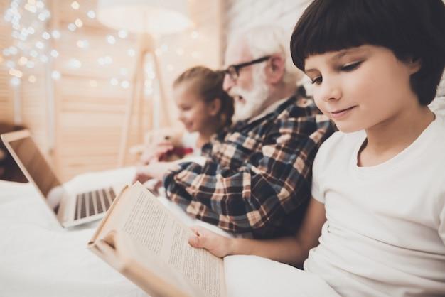 Dziadek i dzieci czytają i oglądają filmy w łóżku.