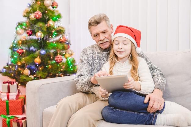 Dziadek i dziewczynka siedzą z tabletem przy choince