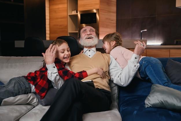 Dziadek i małe wnuki bawią się razem, krzyczą i śmieją się. ciesz się wypoczynkiem z rodziną spędzając weekend w przytulnym domu.