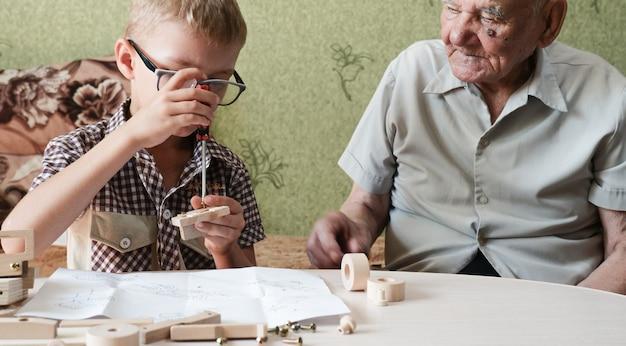 Dziadek i mały chłopiec naprawiają drewniany model samochodu. pojęcie relacji dzieci i osób starszych. trening umiejętności.