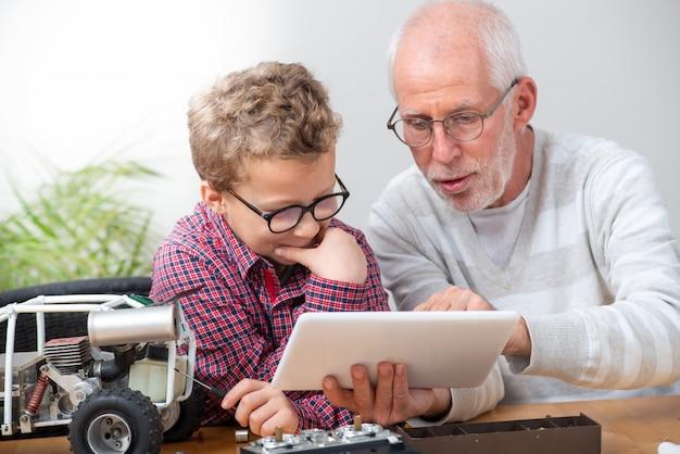 Dziadek i syn mały chłopiec naprawiający model samochodu sterowanego radiowo w domu