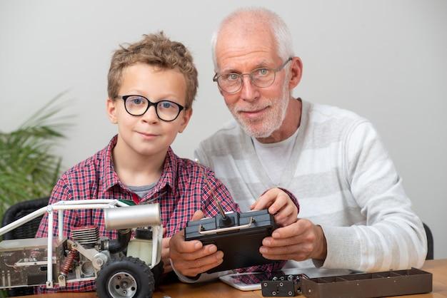 Dziadek i syn mały chłopiec naprawy modelu radiowego samochodu