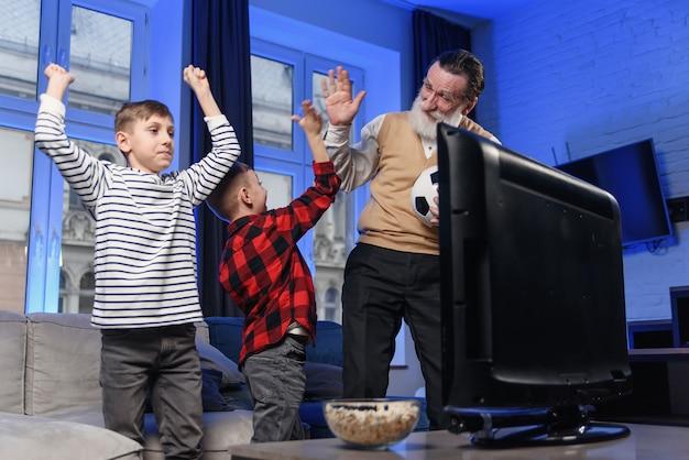 Dziadek i wnuczek ogląda telewizję. dziadek i wnuczek korzystających z domu.