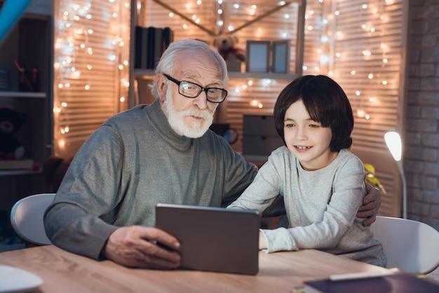 Dziadek i wnuczek, oglądając film na tablecie