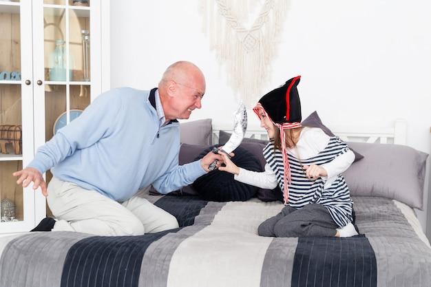 Dziadek i wnuczka grają piratów. dziewczyna w kamizelce i starszy mężczyzna z szablą grają złoczyńców