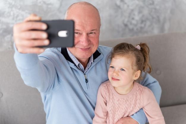 Dziadek i wnuczka, siedząc na kanapie i biorąc selfie