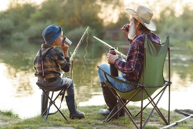 Dziadek i wnuk łowi ryby i pije herbatę