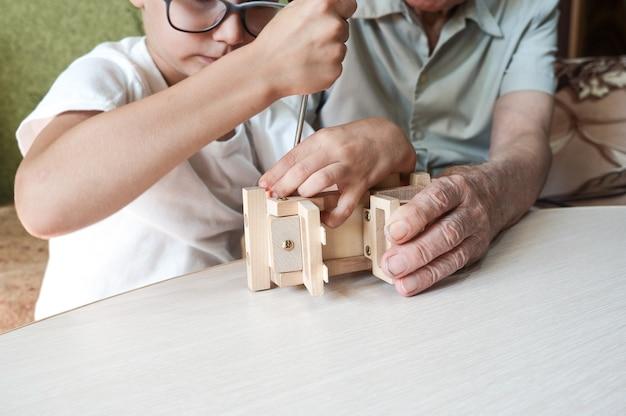 Dziadek i wnuk montują w domu drewniany samochodzik za pomocą śrubokrętów. relacje między pokoleniami.
