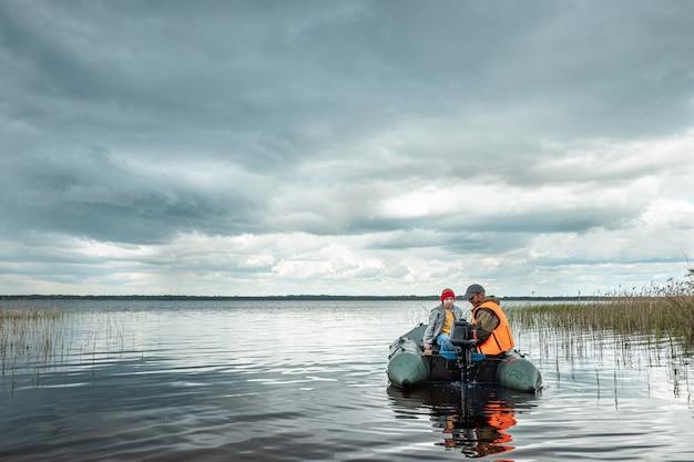Dziadek i wnuk pływają motorówką po jeziorze.