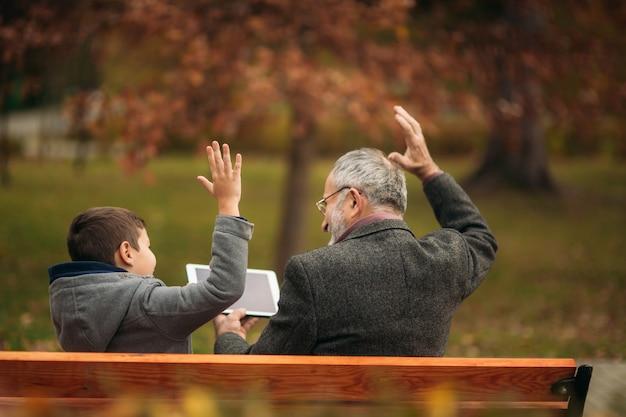Dziadek i wnuk spędzają razem czas w parku. siedzą na ławce. wchodzić w