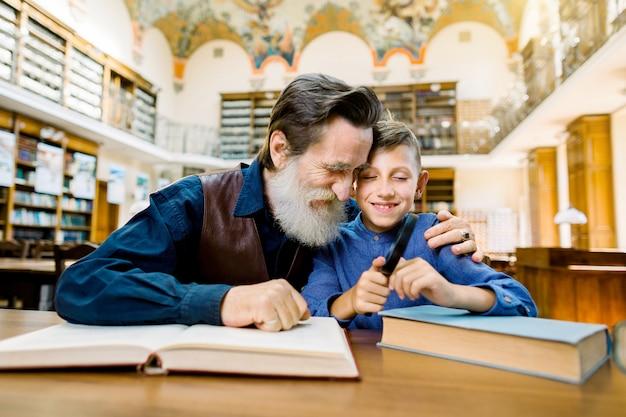 Dziadek i wnuk uśmiecha się i obejmuje, siedząc w starej bibliotece vintage i czytając zabawną ekscytującą książkę. dziadek czyta książkę dla swojego wnuka w bibliotece.