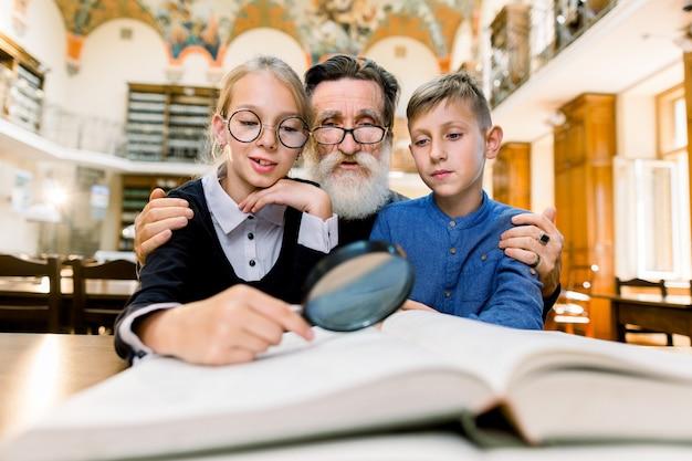 Dziadek i wnuki, nauczyciel i uczniowie, siedzący przy stole w bibliotece