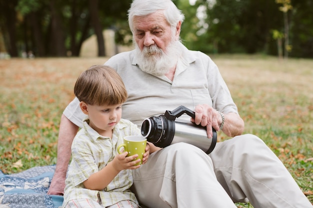 Dziadek nalewający herbatę dla wnuka