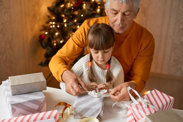 Dziadek pakuje prezenty świąteczne ze swoją uroczą wnuczką