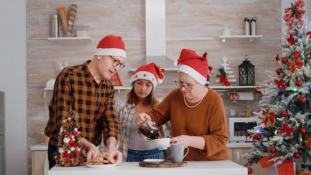 Dziadek podaje dziecku upieczone pyszne ciasteczko, podczas gdy babcia podaje kawę