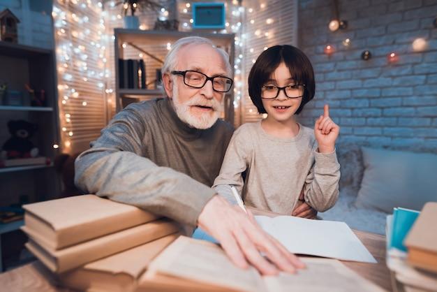 Dziadek pomaga wnukowi w odrabianiu lekcji