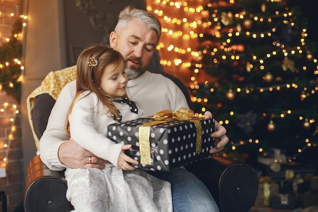 Dziadek siedzi z wnuczką. świętowanie bożego narodzenia w przytulnym domu. mężczyzna w białym swetrze z dzianiny.
