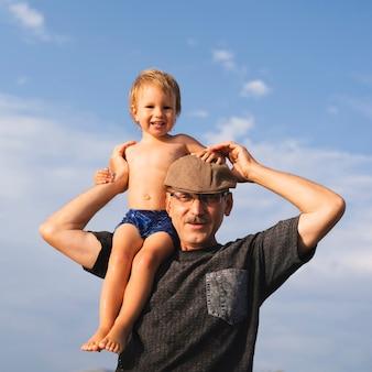 Dziadek trzyma wnuka na ramionach