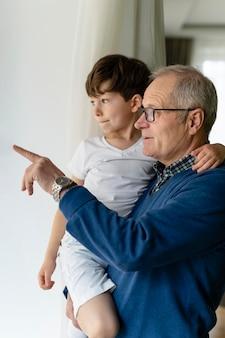 Dziadek trzymający wnuczka przy oknie