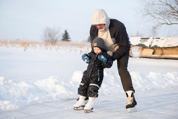Dziadek uczy swojego małego wnuka jazdy na łyżwach na zewnętrznym lodowisku